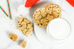 Milk and cookies for Santa Claus. Christmas concept, greeting card. Milk glass and cookies for Santa Claus with Santa`s hat on white marble background, copy Royalty Free Stock Photo