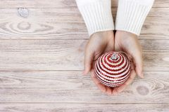 Christmas concept with hand and white ball - christmas tree toy. White round christmas ball in female hand. Wooden Background.  stock photography