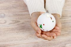 Christmas concept with hand and white ball - christmas tree toy. White round christmas ball in female hand. Wooden Background.  royalty free stock photo