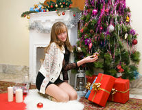 Christmas concept. Happy girl with gifts by the fireplace Stock Photos