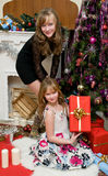 Christmas concept. Happy sisters open Christmas gifts under fir-tree at fireplace Royalty Free Stock Photos