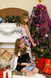 Christmas concept. Happy sisters open Christmas gifts under fir-tree at fireplace Stock Photos