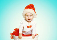 Christmas concept - happy smiling baby in santa red hat gets out of the container Stock Photos