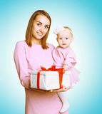 Christmas concept - happy smiling mother and baby in pink dress with box gift Royalty Free Stock Photography