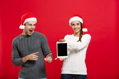 Christmas concept - Happy young couple in christmas sweaters surprising something in digital tablet.  royalty free stock photos
