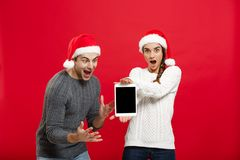 Christmas concept - Happy young couple in christmas sweaters surprising something in digital tablet.  stock image