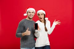 Christmas concept - Happy young couple in christmas sweaters showing thump up gesture with mobile phone Stock Photo