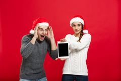 Christmas concept - Happy young couple in christmas sweaters surprising something in digital tablet.  royalty free stock image