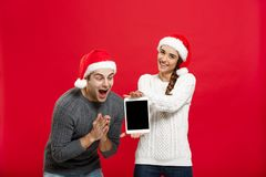 Christmas concept - Happy young couple in christmas sweaters surprising something in digital tablet.  royalty free stock photography