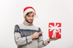 Christmas Concept - Happy young man with beard pointing finger present isolated on white background. Christmas Concept - Happy young man with beard pointing Stock Photography