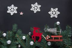 Christmas concept. Holiday card with new year decoration, deer, snowflakes, fir tree branches and balls on black background. T Stock Photos