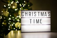 Christmas concept - lihtbox with christmas time text in dark room with christmas tree. Christmas concept - lihtbox with christmas time text in dark room with stock photos
