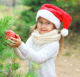Christmas concept - little child in santa red hat with ball Royalty Free Stock Images