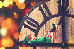 Christmas concept. Little Elf on clockwise royalty free stock photo