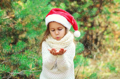 Christmas concept - little girl child in santa red hat blowing on snow in hands Stock Images
