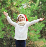 Christmas concept - little girl child in santa red hat enjoying snow Stock Images