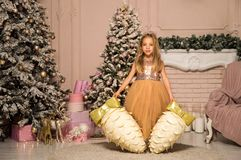 Christmas concept. A little girl in an elegant dress is surrounded by large decorative cones near the festive Christmas tree