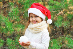 Christmas concept - little smiling girl child in santa red hat with snowball Stock Photo