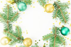 Christmas concept made of round frame with fir branches, glass balls and golden confetti on white background. Flat lay, top view. Christmas concept made of round royalty free stock photography