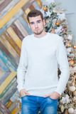 Christmas concept, male fashion. Handsome young man in elegant pullover posing in luxurious apartments decorated for stock photos