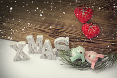 Christmas concept with ornament birds at birdnest. Closeup photograph of ornament birds at nest next to xmas letters Royalty Free Stock Photography