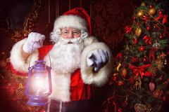 Fairytale santa claus. Christmas concept. Portrait of a fairytale Santa Claus standing with lantern and wonders. Beautiful home decorated for Christmas. Time of Royalty Free Stock Image