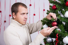 Christmas concept - portrait of handsome man decorating Christma Stock Photo