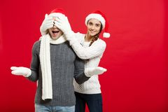 Christmas Concept - portrait lovely girlfriend surprising close her boyfriend eyes in Christmas day.  Royalty Free Stock Images