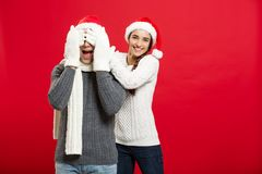 Christmas Concept - portrait lovely girlfriend surprising close her boyfriend eyes in Christmas day.  Stock Photos