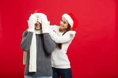 Christmas Concept - portrait lovely girlfriend surprising close her boyfriend eyes in Christmas day.  Royalty Free Stock Image