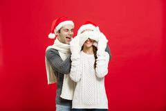 Christmas concept - Portrait of a romantic young boyfriend surprising girlfriend over red studio background.  Stock Image