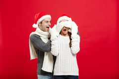 Christmas concept - Portrait of a romantic young boyfriend surprising girlfriend over red studio background. Christmas concept - Portrait of a romantic young Royalty Free Stock Photo