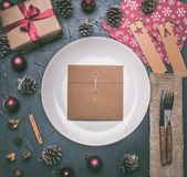 Christmas concept, postcard, gift box, Christmas toys and cones, on grey background, lined around a white plate stock photos