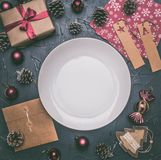 Christmas concept, postcard, gift box, Christmas toys and cones, on grey background, lined around a white plate royalty free stock images