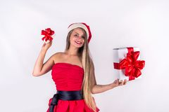 Christmas concept. Pretty girl wearing red dress holding present gift box isolated Royalty Free Stock Image