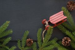 Christmas concept with red sleigh, pine cones and fir tree branch on black background. Top view and copy space Stock Photo
