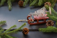 Christmas concept with red sleigh, pine cones and fir tree branch on black background. copy space. Christmas concept with red sleigh, pine cones and fir tree Stock Image