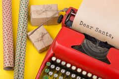 Christmas concept - typewriter with the text & x22;Dear Santa,& x22; gift boxes and wrapping paper on yellow background. Christmas concept - red typewriter with Royalty Free Stock Images
