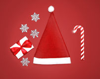 Christmas concept - santa cap, gift box, snowflakes and candy Stock Images