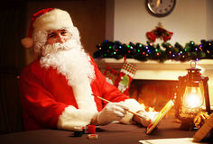 Christmas concept. Santa Claus makes toy, close up. Christmas decorations on wooden table Stock Images