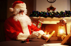 Christmas concept. Santa Claus makes toy, close up. Christmas decorations on wooden table Royalty Free Stock Photography