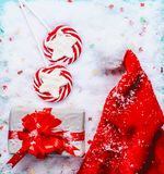 Christmas concept. Santa hat with Christmas gift box and red candy lollipops on snow stock photo