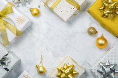 Christmas concept - silver and gold presents with confetti and ribbon royalty free stock image