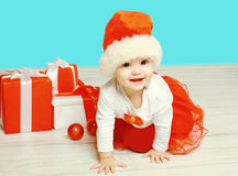Christmas concept - smiling child in santa red hat with boxes gifts crawls on floor Royalty Free Stock Images