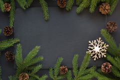 Christmas concept with snowflakes, pine cones and fir tree branch on black background. Top view. Christmas concept with snowflakes, pine cones and fir tree Royalty Free Stock Image