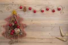 Vintage Christmas tree with burlap balls, cones, wooden sticks and red apples on beige wood background. Royalty Free Stock Images