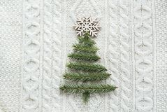 Christmas concept with spruce, fir-tree, snowflakes, on white knitted background. Holiday card. Vintage style. Stock Photography