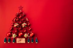 Christmas concept. Top view of gift box with red ball and bell in shape of Christmas tree on red background stock photos
