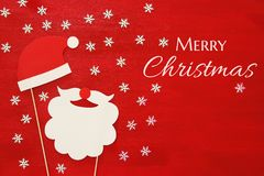 Christmas concept top view image. Santa claus beard and hat on red wooden background Stock Photo