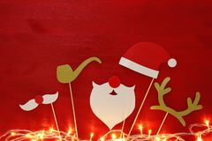 Christmas concept top view image. Santa claus beard and hat on red wooden background. Royalty Free Stock Photos